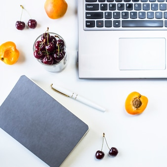 Werkplek met laptop en kladblok op witte tafel met bessen en fruit snack