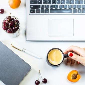 Werkplek met laptop en notitieblok op een witte tafel met bessen en fruit snack