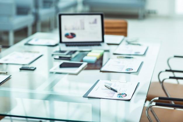 Werkplek met laptop en werkdocumenten voor het zakelijke team in een modern kantoor