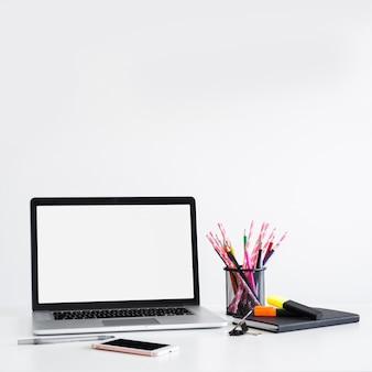Werkplek met laptop in de buurt van de pen, potloden in kan en smartphone
