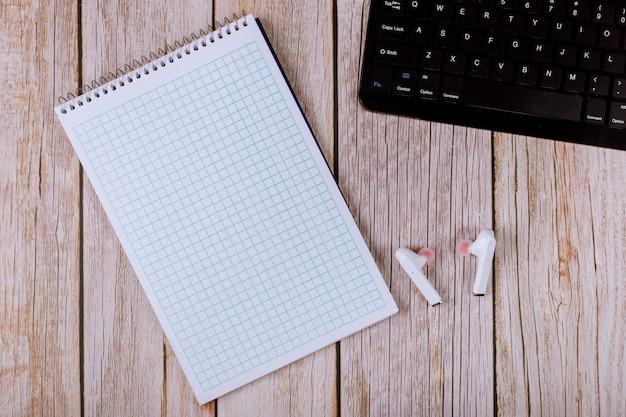 Werkplek met laptop toetsenbord een bureau met papieren notitieblok voor notities geschreven, draadloze hoofdtelefoons