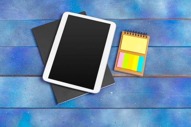 Werkplek met lege digitale tablet, papier op blauwe houten werktafel. bovenaanzicht schot