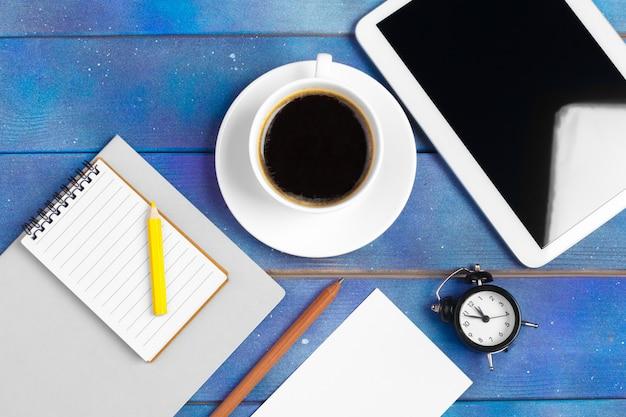 Werkplek met lege digitale tablet, papier op blauwe houten werktafel.