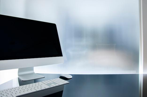 Werkplek met moderne computer op glazen tafel, bespotten zwart scherm, kamerplant en benodigdheden.