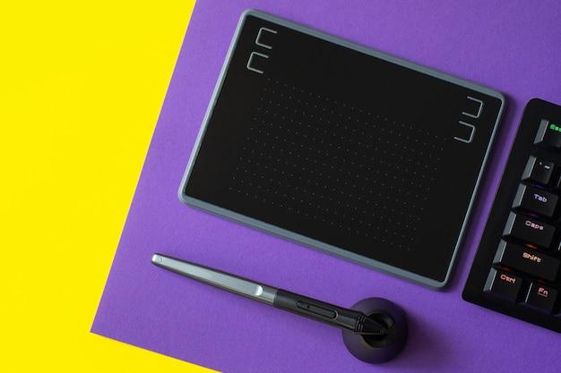 Werkplek met notebook, pentablet, toetsenbord, op paars en geel