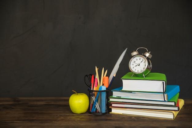 Werkplek met schoolboeken en wekker