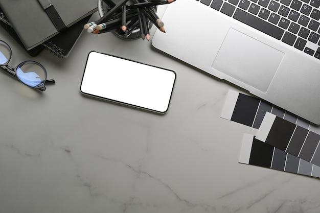 Werkplek met slimme telefoon, laptopcomputer, kleurstaal en notitieboekje op marmeren achtergrond.