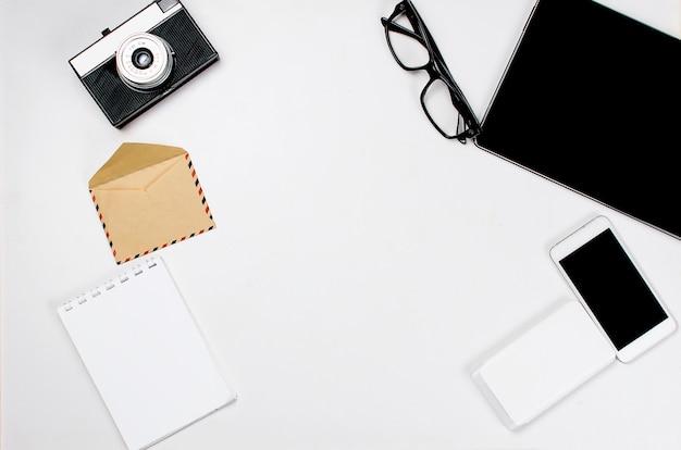 Werkplek met tablet, smartphone, pen, notitieblok en glazen.