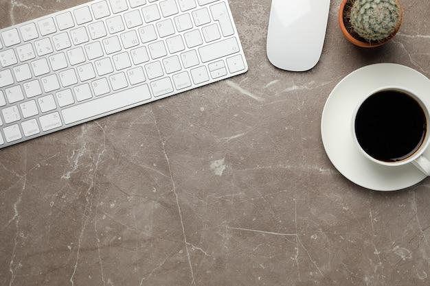 Werkplek met toetsenbord, muis, koffie en cactus