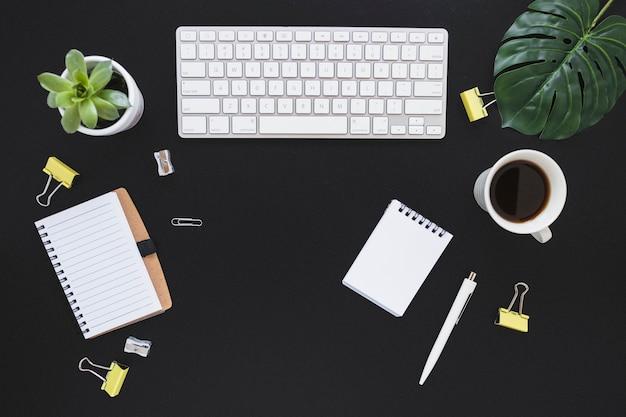 Werkplek met toetsenbordbeker en briefpapier
