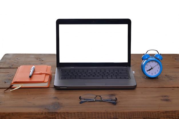 Werkplek met wekker laptop en notebook