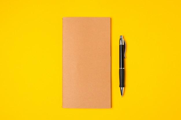 Werkplek, notitieblok en pen op fel geel