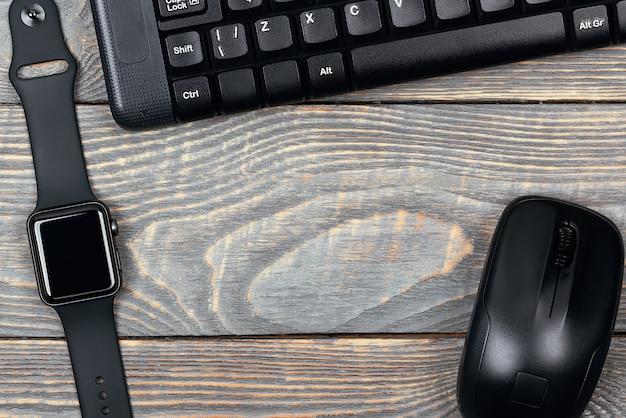 Werkplek slim horloge, toetsenbord, muis op een houten tafel.