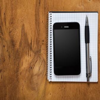 Werkplek. telefoon en notitieblok op tafel
