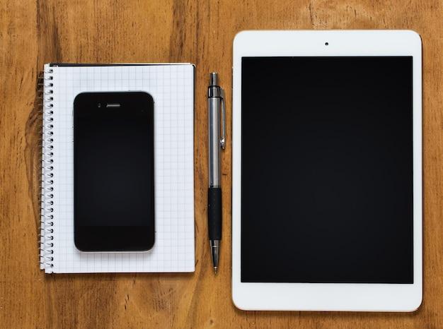 Werkplek. telefoon, tablet en notitieblok op tafel
