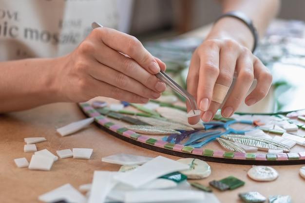 Werkplek van de handen van de mozaïekmeester die het gereedschap vasthoudt voor mozaïekdetails tijdens het maken van...