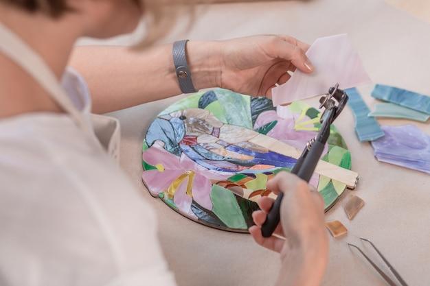 Werkplek van de mozaïekmeester: vrouwenhanden die gereedschap vasthouden voor mozaïekdetails tijdens het maken van een mozaïek