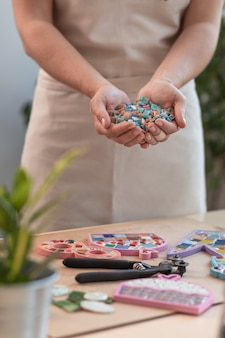 Werkplek van de mozaïekmeester: vrouwenhanden met mozaïekdetails tijdens het maken van een mozaïek