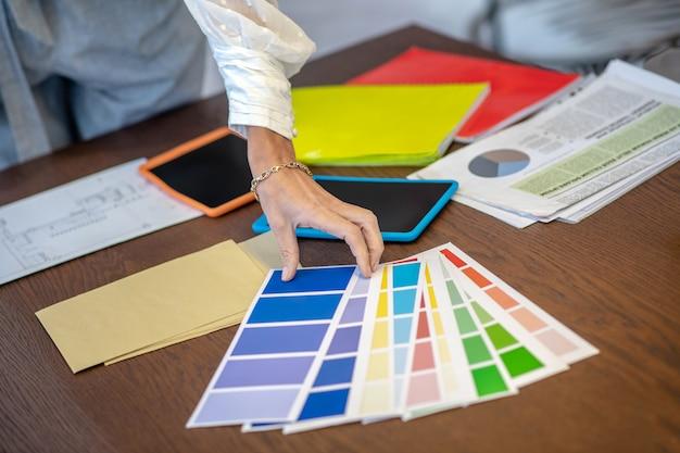 Werkplek van de ontwerper. elegante vrouwelijke hand met een armband om haar pols boven de tafel in de buurt van de kleurenschaal.