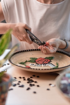 Werkplek van een mozaïekmeester: vrouwelijke handen leggen een mozaïekelement op tafel