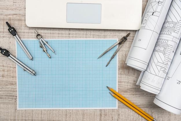 Werkplek van ingenieur. bovenaanzicht van laptop-, kladblok- en tekengereedschappen
