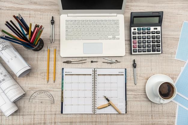 Werkplek van ingenieur met laptop, kladblok en tekengereedschappen