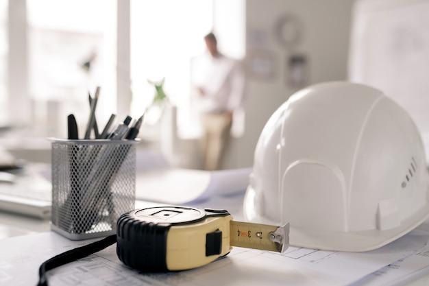 Werkplek van ingenieur met veiligheidshelm, meetlint, stelletje potloden en schetsen op de achtergrond van de mens