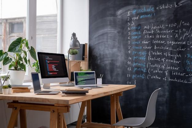 Werkplek van it-ingenieur bij loket met twee laptops, computermonitor, enkele boeken en schriften, lamp en huiselijke planten