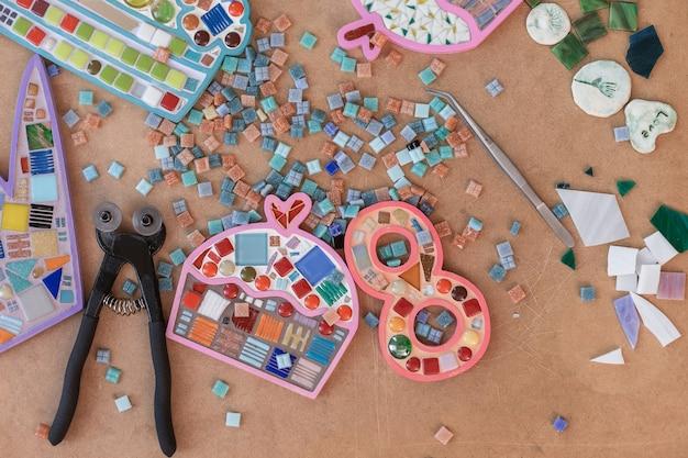 Werkplek van mozaïekmaker: materiaal en gereedschap op houten tafel