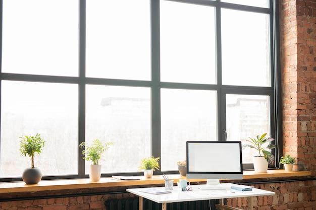 Werkplek van officemanager met klein bureau bij vensterbank, computermonitor en groep benodigdheden