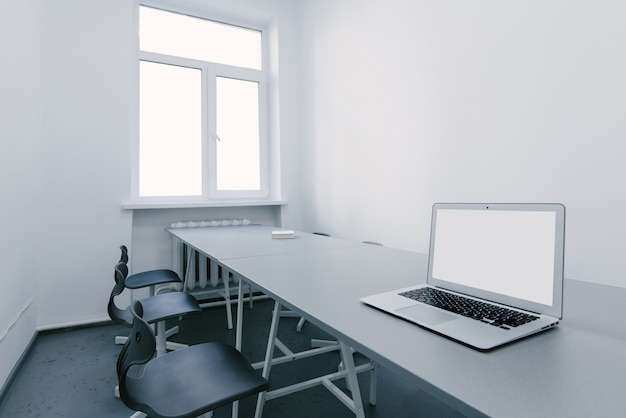 Werkplek voor een laptop in een licht kantoor. onderhandelingsruimte op kantoor. laptop is op het bureau in het kantoor.