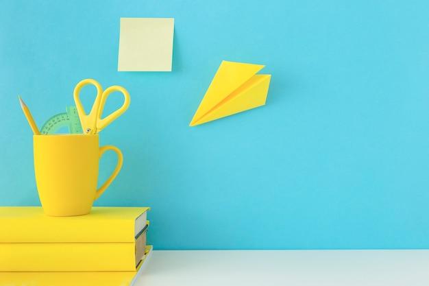Werkplek voor onderzoeken met gele notitieblokken en papieren vliegtuig