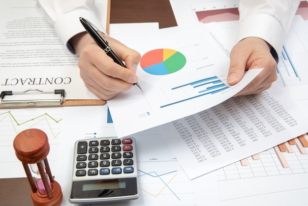 Werkplek zakenman. contracten, grafieken en grafieken op het bureau.