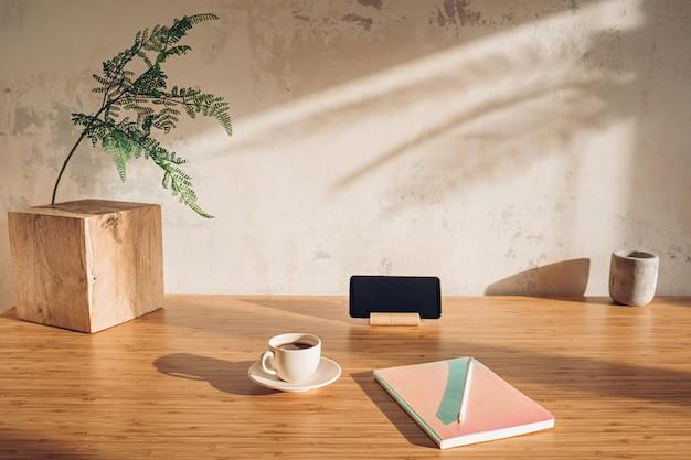 Werkplek zonder iets overbodigs. bureau met mobiele telefoon, notitieboekje en kopje koffie in zonlicht