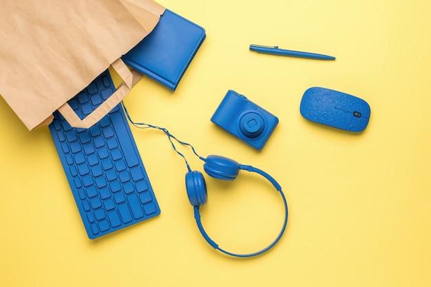 Werkplekaccessoires komen uit een papieren zak op een gele achtergrond. koop artikelen voor op kantoor. plat leggen.
