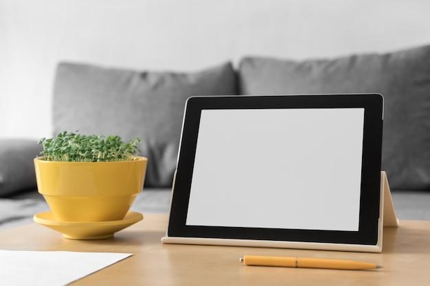 Werkplekaccessoires voor online werken. tablet, pen en bloempot met verse microgreen basilicum op tafel, grijze sofa achtergrond.