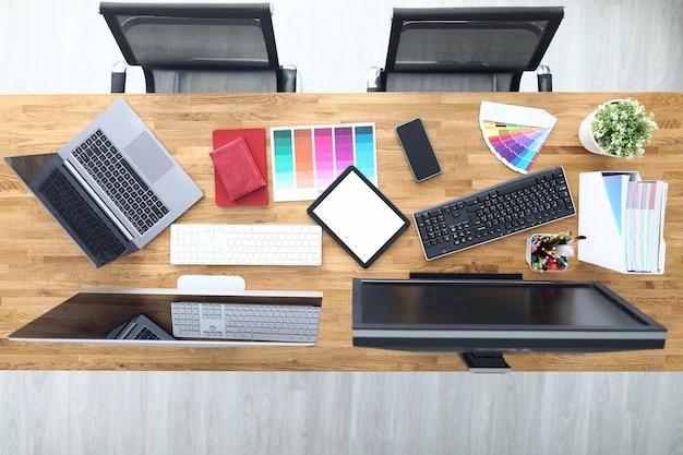 Werkplekken in bureautafel stoelen tablet smartphone kleurenpalet potloden tablet toetsenbord beeldschermen. werkplek lay-out concept