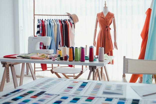 Werkplekken van kledingontwerpers met naaimachines, houten mannequins, kledingroedes, van startende bedrijfsconcept.