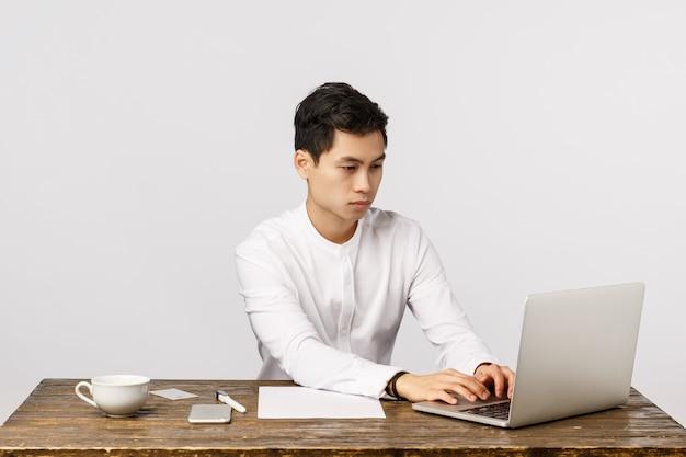 Werkproces, bedrijfs- en bedrijfsconcept. de knappe aziatische zakenman in kraagoverhemd, zittend bureau bereidt rapport voor, werkend met laptop, die cliënten via post contacteren