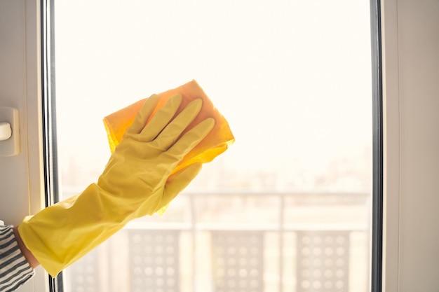 Werkproces. bewuste huisvrouw die rubberen handschoenen draagt tijdens het wassen van ramen in de keuken