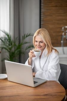 Werkproces. mooie blonde vrouw zit op de laptop en kijkt attent