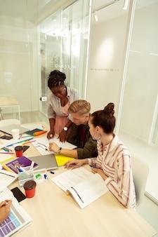 Werkproces. opgetogen internationale leraar die in de buurt van haar student staat terwijl ze de taak controleert