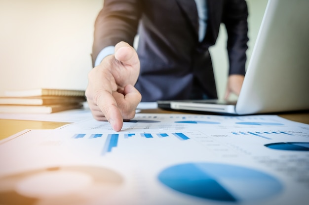 Werkproces opstarten. zakenman werken met nieuw financieel project op kantoor met laptop, tablet en grafiedata documenten op zijn bureau
