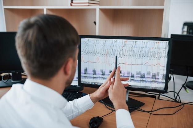 Werkproces. polygraaf examinator op kantoor met de apparatuur van zijn leugendetector