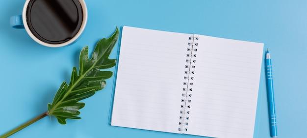Werkruimte blauwe set van notitieblok, pen, groen blad en koffiekopje, bovenaanzicht