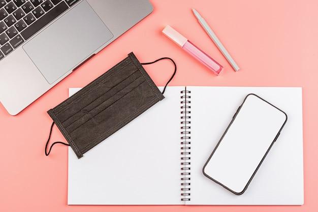 Werkruimte bureau met laptop, leeg notebook, medische masker op roze