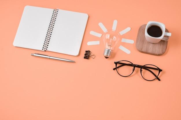 Werkruimte bureau stijl ontwerp kantoorbenodigdheden met pen, kladblok, brillen, kopje koffie en gloeilamp