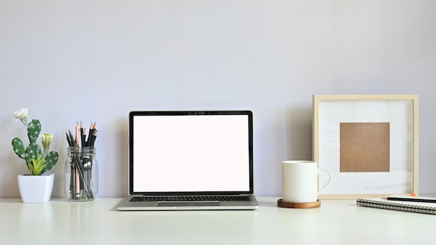 Werkruimte computer laptop, cactus, potlood, koffie en foto frame op tafel.