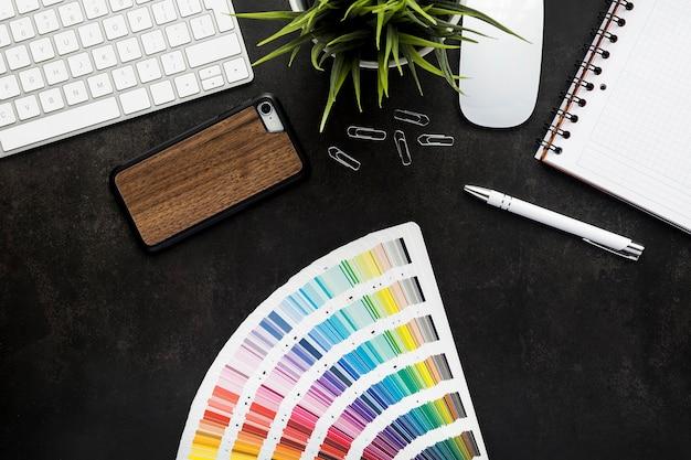 Werkruimte grafisch ontwerper met zwart bureau en toetsenbord, plant, muis, notitieblok, smartphone en pen