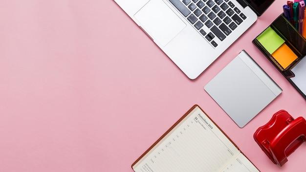 Werkruimte kantoorbenodigdheden en laptop op roze achtergrond